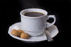 Taza blanca de la porcelana de coffie con tres galletas italianas del amaretti Fotos de archivo libres de regalías