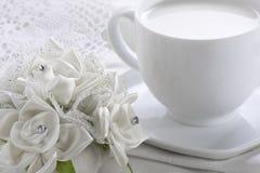 Taza blanca de leche y de rosas Imagenes de archivo