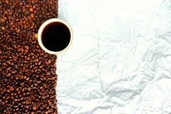 Taza blanca de los granos de café y el papel Foto de archivo