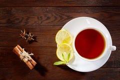 Taza blanca de té con los palillos de canela, el limón, las hojas de menta y el tamiz del té en la tabla rústica de madera Fotografía de archivo libre de regalías