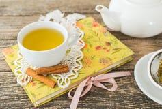Taza blanca de té de manzanilla y libro en la tabla Fotografía de archivo
