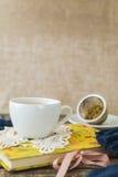 Taza blanca de té de manzanilla y libro en la tabla Imagen de archivo libre de regalías