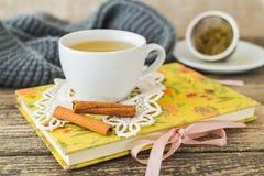 Taza blanca de té de manzanilla y libro en la tabla Fotografía de archivo libre de regalías
