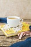 Taza blanca de té de manzanilla y libro en la tabla Foto de archivo