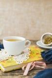 Taza blanca de té de manzanilla y libro en la tabla Imagenes de archivo
