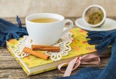 Taza blanca de té de manzanilla y libro en la tabla Imágenes de archivo libres de regalías