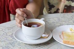 Taza blanca de té a disposición en el fondo de la tabla Fotografía de archivo libre de regalías