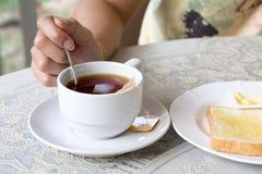 Taza blanca de té a disposición en el fondo de la tabla Imagen de archivo libre de regalías