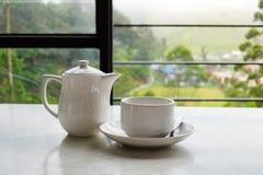 Taza blanca de té y tetera en la tabla de mármol blanca Foto de archivo