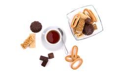 Taza blanca de té y una selección de dulces Imagen de archivo libre de regalías