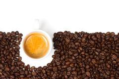 Taza blanca del café express sentada en los granos de café Foto de archivo libre de regalías