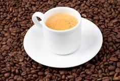 Taza blanca del café express sentada en los granos de café Imagen de archivo