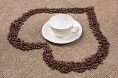 Taza blanca en de arpillera con el corazón del café foto de archivo libre de regalías