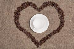 Taza blanca en de arpillera con el top del corazón del café foto de archivo libre de regalías
