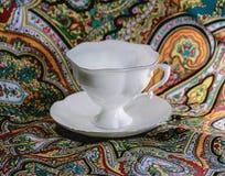 Taza blanca en el color de fondo del mantón Fotos de archivo libres de regalías