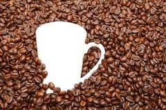 Taza blanca en granos de café Fotos de archivo