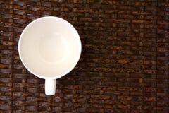 Taza blanca en la tabla de madera de la armadura Imagen de archivo