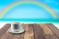 Taza blanca en la tabla y el arco iris borroso en fondo Fotos de archivo libres de regalías