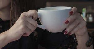 Taza blanca grande de americano en las manos femeninas Fotografía de archivo