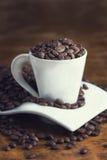 Taza blanca llena de granos de café Foto de archivo libre de regalías