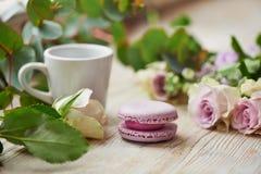 Taza blanca, macarrones púrpuras de la torta, flores frescas Imagen de archivo libre de regalías