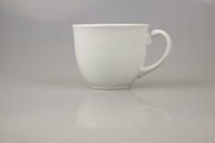 taza blanca para el café o el té en el fondo blanco Foto de archivo