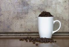 Taza blanca por completo de granos de café Fotografía de archivo