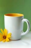 Taza blanca y flor amarilla Fotografía de archivo
