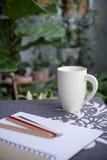 Taza blanca y un libro Fotos de archivo libres de regalías