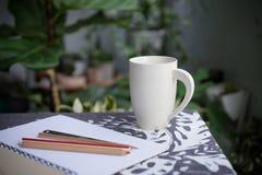 Taza blanca y un libro en jardín Imagen de archivo libre de regalías