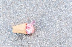 Taza caída del helado en el pavimento de tierra del asfalto y derretida de la opinión del calor desde arriba Fotos de archivo libres de regalías