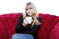 Taza cabelluda rubia joven de la bebida de la muchacha de café en el sofá rojo en frente fotografía de archivo libre de regalías