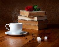 Taza caliente de café fresco en la tabla y la pila de madera de libros Imágenes de archivo libres de regalías