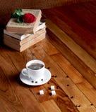 Taza caliente de café fresco en la tabla y la pila de madera de libros Imagen de archivo libre de regalías