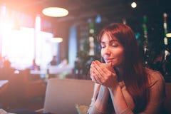 Taza caliente de té con las manos de la mujer café femenino hermoso de la taza en el restaurnt Muchacha roja del pelo Fotografía de archivo