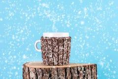 Taza caliente de té en el registro de madera, está nevando y fondo azul fotos de archivo libres de regalías