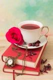 Taza caliente de té y de libros rojos Foto de archivo