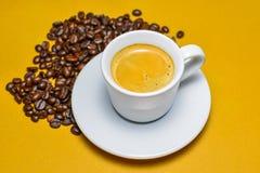 Taza caliente del café express con los granos de café Fotografía de archivo