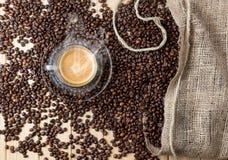 Taza caliente del café express sobre la tabla de madera por completo de granos de café Foto de archivo libre de regalías