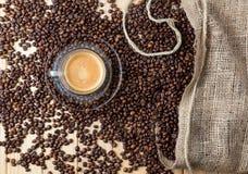 Taza caliente del café express sobre la tabla de madera por completo de granos de café Fotografía de archivo libre de regalías