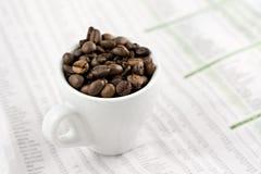 Taza clásica del café express en las paginaciones financieras imagen de archivo