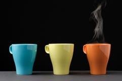 Taza colorida tres con vapor Foto de archivo libre de regalías