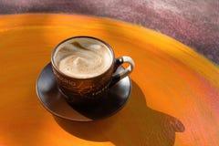 Taza con café caliente de la leche en una tabla de madera colorida en un café fotos de archivo
