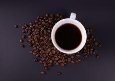 Taza con café fuerte y la opinión superior dispersada de los granos de café imagen de archivo libre de regalías