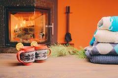 Taza con el ornamento de la Navidad cerca de la chimenea Taza en paño hecho punto Fotos de archivo
