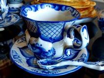 Taza con el platillo y la cucharilla el estilo de Gzhel en el fondo de las crepes rusas del blinov Celebración de Maslenitsa Gzhe fotografía de archivo libre de regalías