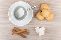Taza con la bolsita de té, los palillos de canela, la galleta de torta dulce y el azúcar Foto de archivo