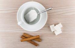 Taza con la bolsita de té, los palillos de canela y los pedazos de azúcar Imagenes de archivo