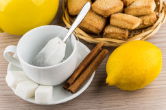 Taza con la bolsita de té, azúcar y canela, limón y galletas Foto de archivo libre de regalías