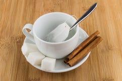 Taza con la bolsita de té, el azúcar y el canela en la tabla Foto de archivo